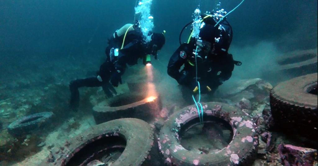 Bildet viser to dykkere som lyser på gamle dekk. Foto: Gisle Johnsen – The Dale Oen Experience.